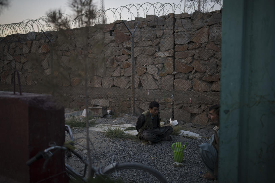 Two men detained by Taliban fighters sit at the entrance of a police station in Kabul, Afghanistan, Tuesday, Sept. 21, 2021. The Taliban are shifting from being warriors to an urban police force. (AP Photo/Felipe Dana)