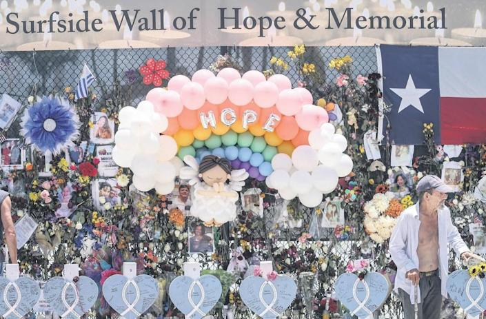 Wooden hearts with the names of victims are erected along side the photos, flowers, and other memorial items as visitors walk through the memorial site of the partial collapse of the Champlain Towers South in Surfside, on Sunday, July 11, 2021.