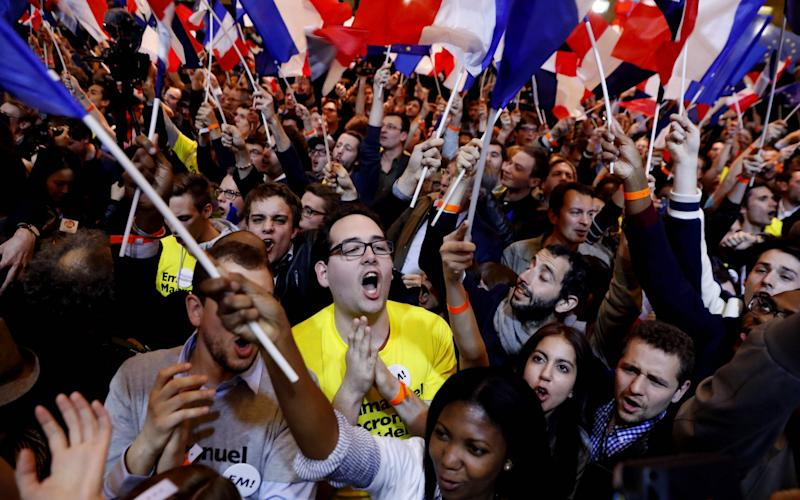 Emmanuel Macron's supporters cheer following the announcement he was on course to qualify for the second round - Credit: PATRICK KOVARIK/AFP