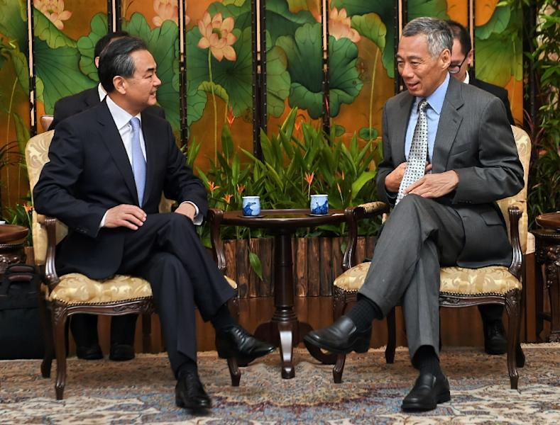 Chinese Foreign Minister Wang Yi (L) talks with Singaporean Prime Minister Lee Hsien Loong at the Istana presidential palace in Singapore on August 3, 2015 (AFP Photo/Roslan Rahman)
