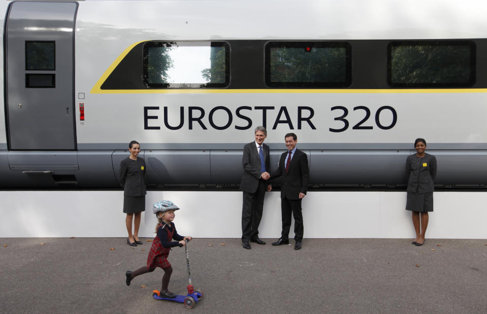 A child rides her scooter past Britain's Transport Minister Philip Hammond (2nd L) and Eurostar's Chief Executive Officer Nicolas Petrovic, as they shake hands next to a new Eurostar train, during a media event, in central London, October 7, 2010. German industrial group Siemens will supply 10 next-generation high-speed trains to Eurostar as part of a 700 million pound ($1 billion) investment in the Channel Tunnel operator's fleet. REUTERS/Andrew Winning (BRITAIN - Tags: BUSINESS POLITICS SOCIETY TRANSPORT TRAVEL)