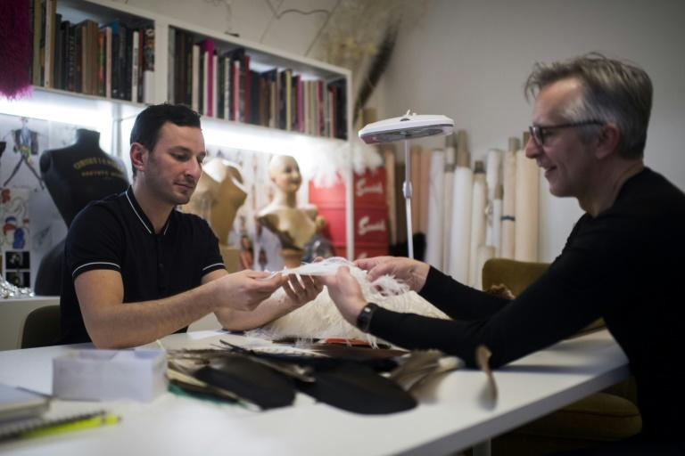 Serkan Cura, left, one of the world's top plumassiers, examines a feather design with Olivier Portais of the French wedding dress label Cymbeline