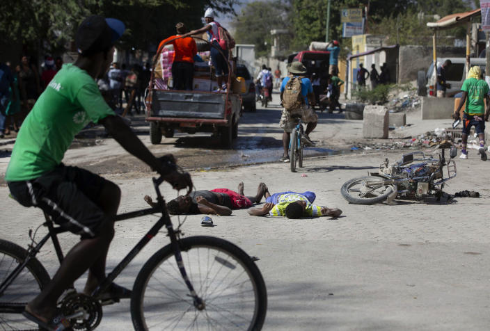 The bodies of two inmates lie on the street outside the Croix-des-Bouquets Civil Prison after an attempted breakout, in Port-au-Prince, Haiti, Thursday, Feb. 25, 2021. At least seven people were killed and one injured after eyewitnesses told The Associated Press that several inmates tried to escape from the prison in Haiti's capital. (AP Photo/Dieu Nalio Chery)