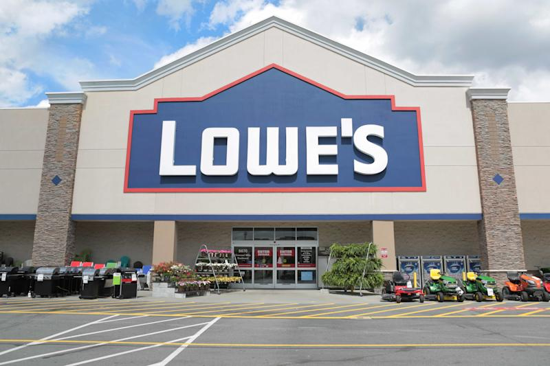 Lowe's storefront with lawn mowers and plants.