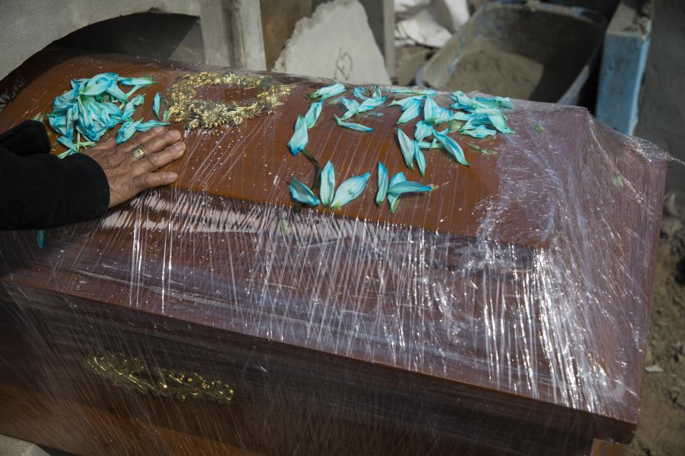"""A relative of Joaquin Alonso touches the coffin of the 58-year-old who died of COVID-19 during his burial at the cemetery """"Martires 19 de Julio"""" in Comas on the outskirts of Lima, Peru, Tuesday, July 28, 2020. Peruvian authorities and the Pan American Health Organization are investigating whether the country failed to classify just over 27,000 deaths as caused by the novel coronavirus, a figure that could more than double the country's official death toll from the disease. (AP Photo/Rodrigo Abd)"""