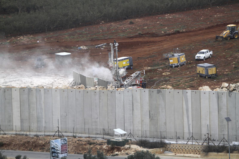 """An Israeli military digger works on the Lebanese-Israeli border next to a wall that was built by Israel in the southern village of Kafr Kila, Lebanon, Tuesday, Dec. 4, 2018. The Israeli military launched an operation on Tuesday to """"expose and thwart"""" tunnels it says were built by the Hezbollah militant group that stretch from Lebanon into northern Israel. (AP Photo/Mohammed Zaatari)"""