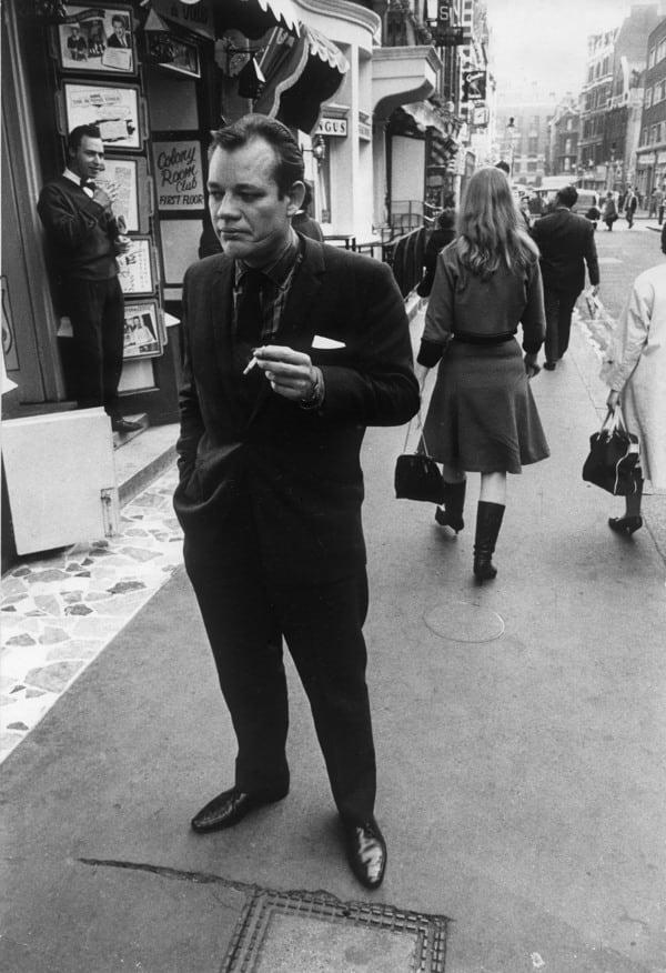 """<div class=""""inline-image__caption""""> <p>Writer Frank Norman outside the Colony Room in London's Soho</p> </div> <div class=""""inline-image__credit""""> Daniel Farson / Tales from The Colony Room </div>"""