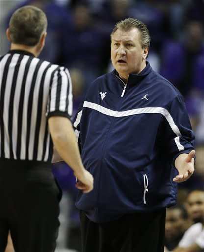 West Virginia head coach Bob Huggins, right, talks with an official during the first half of an NCAA college basketball game against Kansas State in Manhattan, Kan., Monday, Feb. 18, 2013. (AP Photo/Orlin Wagner)