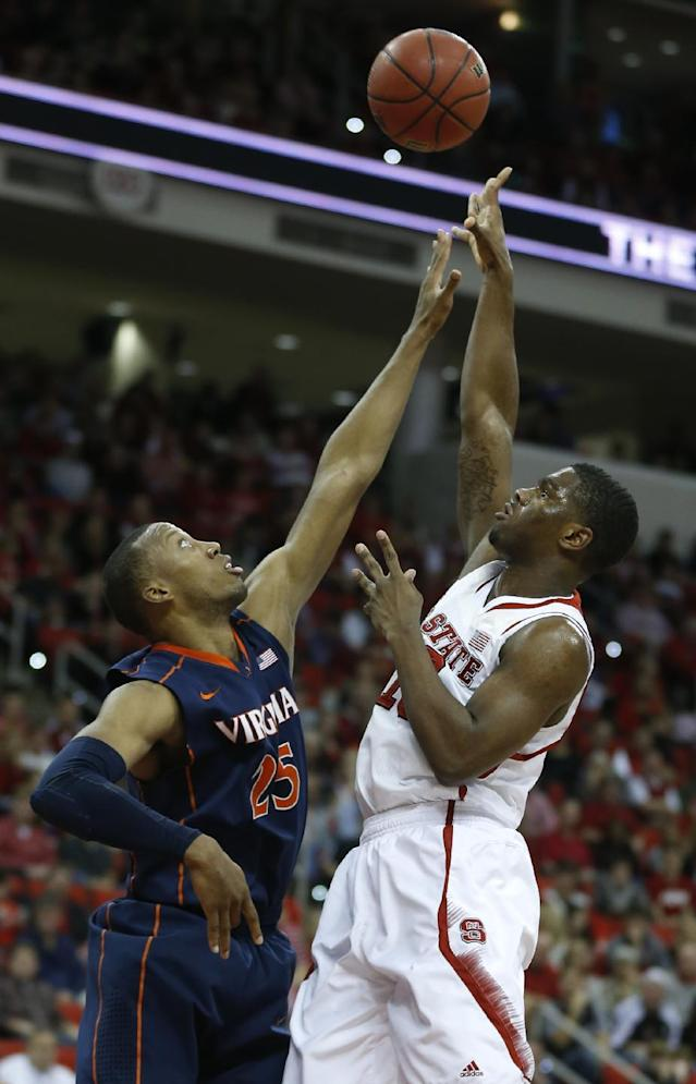 North Carolina State's Lennard Freeman, right, shoots over pressure by Virginia's Akil Mitchell (25) during the first half of an NCAA college basketball game in Raleigh, N.C., Saturday, Jan. 11, 2014. (AP Photo/The News & Observer, Ethan Hyman)