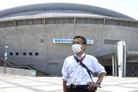 Olympic volunteer Atsushi Muramatsu poses for a photo in front of Sekisui Heim Super Arena, which was used as a morgue after the 2011 earthquake, also known as the Great East Japan Earthquake, in Rifu, Japan, Thursday, July 29, 2021. The arena is situated next to Miyagi Stadium, which is used for soccer matches during the 2020 Summer Olympics, where he is serving as a volunteer. Muramatsu has made business-card size flyers to express gratitude for support from overseas. He plans to hand them out to foreign media. (AP Photo/Chisato Tanaka)