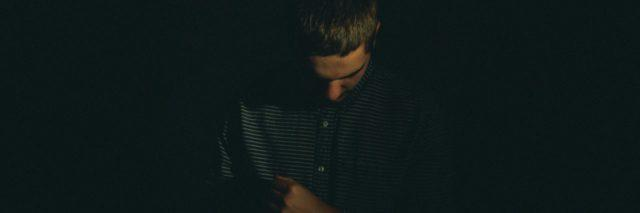 man in the dark looking down and holding one arm over his chest
