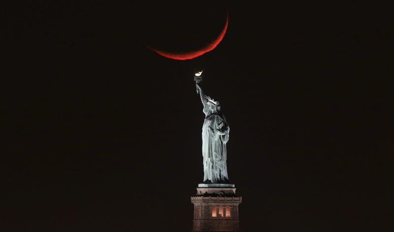 A crescent moon sets behind the Statue of Liberty on Jan. 19, 2018 in New York City. (Gary Hershorn via Getty Images)