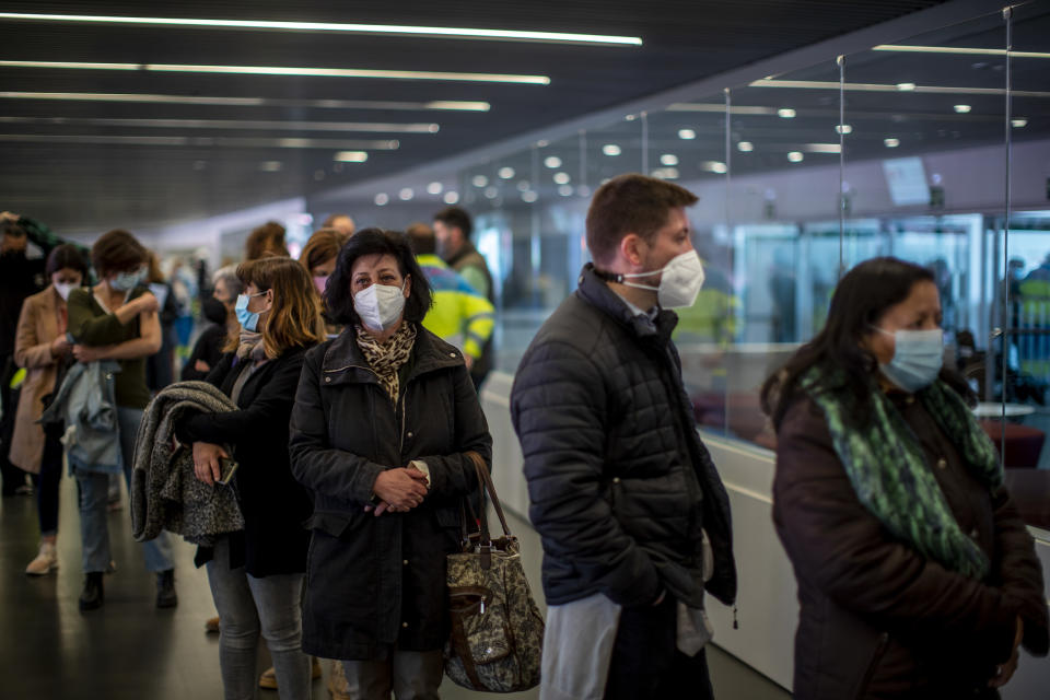 People queue after receiving the COVID-19 vaccine, during a mass vaccination campaign at Wanda Metropolitano stadium in Madrid, Spain, Wednesday, March 24, 2021. Spain resumed the use of the AstraZeneca vaccine on Wednesday by extending it to adults up to 65 years old. (AP Photo/Manu Fernandez)