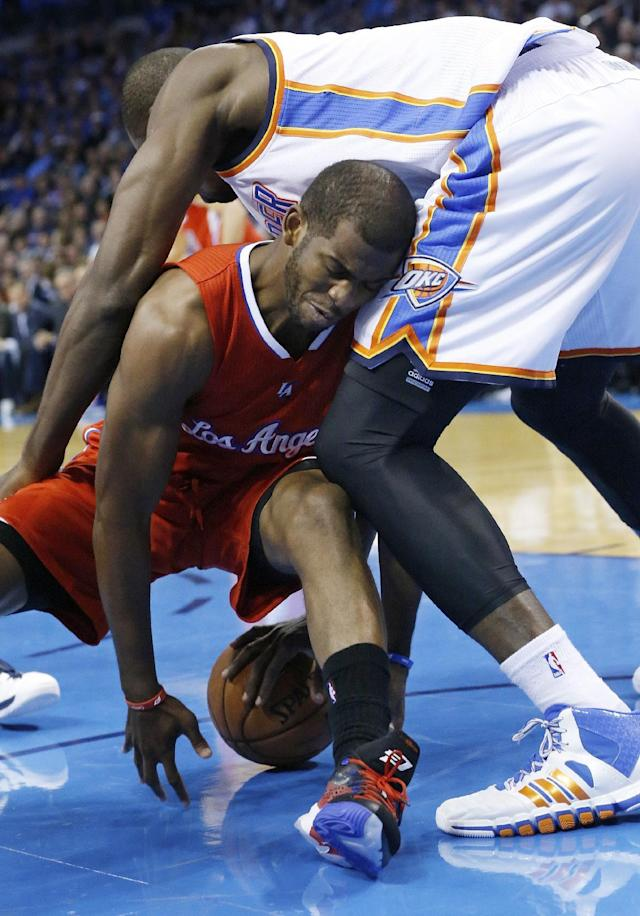 Los Angeles Clippers guard Chris Paul, bottom, fights with Oklahoma City Thunder forward Serge Ibaka, top, for the ball in the first quarter of an NBA basketball game in Oklahoma City, Thursday, Nov. 21, 2013. (AP Photo/Sue Ogrocki)