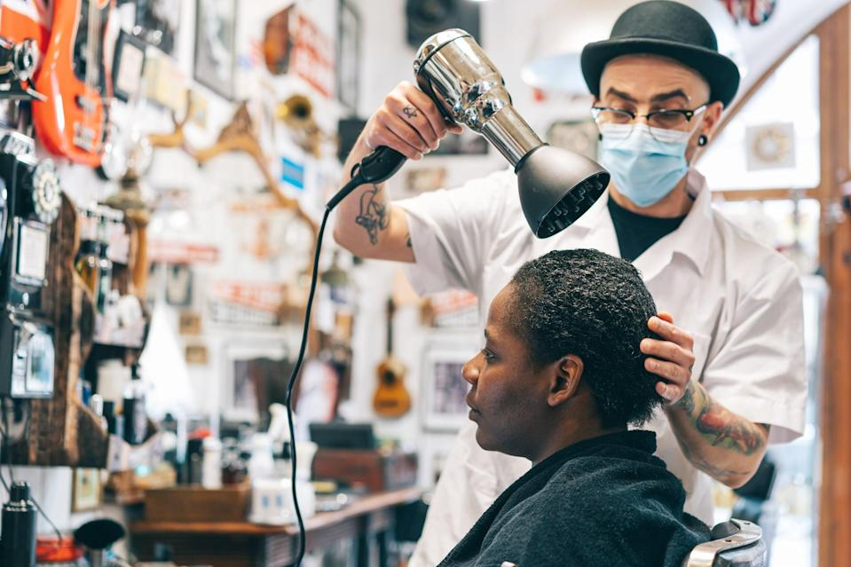 Male hairdresser wearing protective face mask and drying afro woman's hair with hair dryer in beauty studio