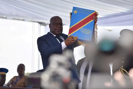 FILE PHOTO: Felix Tshisekedi holds up the constitution during his presidential the inauguration ceremony in Kinshasa, Democratic Republic of Congo, January 24, 2019. REUTERS/Olivia Acland/File Photo