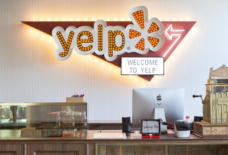 Yelp front desk with company logo on wall behind it