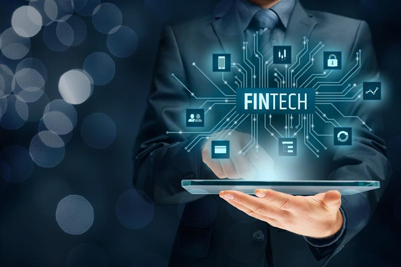 The word Fintech pops out of a tablet held by a man in a suit viewed from the neck-down.