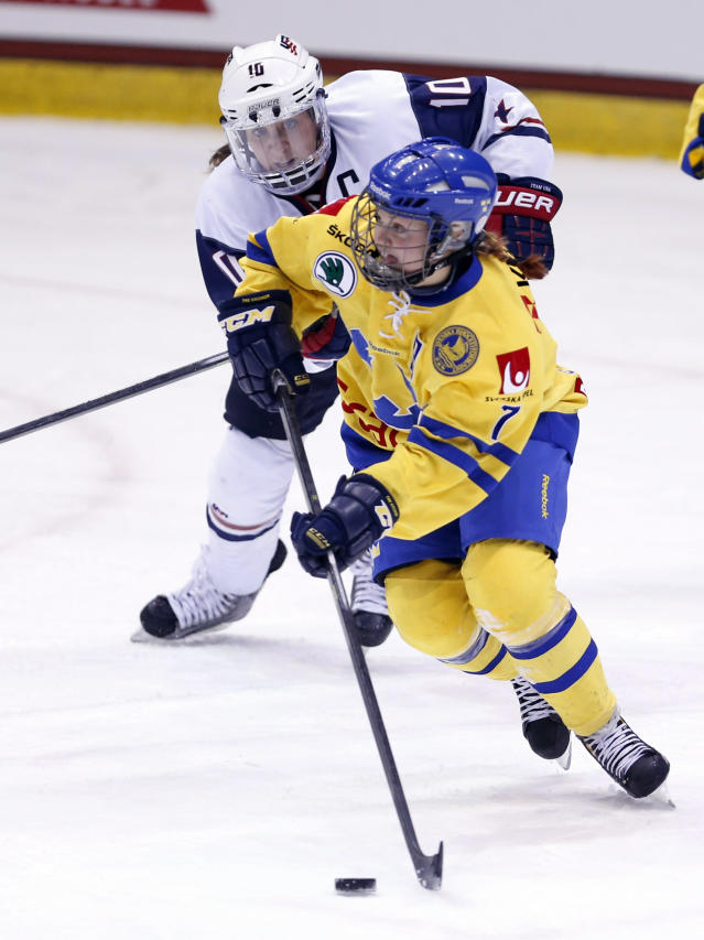 Sweden's Johanna Olofsson (7) moves the puck away from USA's Meghan Duggan (10) during the second period of a Four Nations Cup women's hockey game on Tuesday, Nov. 5, 2013, in Lake Placid, N.Y. (AP Photo/Mike Groll)