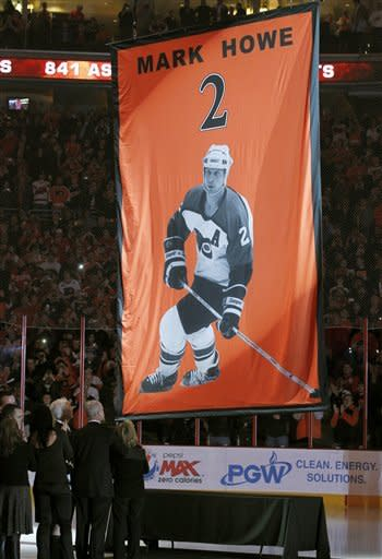 Gordie Howe, Mark Howe, second from right, and Ginger Howe, right, watch as NHL Hall of Famer Mark Howe's jersey number is raised during a ceremony to retire the number, before an NHL hockey game between the Philadelphia Flyers and the Detroit Red Wings on Tuesday, March 6, 2012, in Philadelphia. (AP Photo/Alex Brandon)