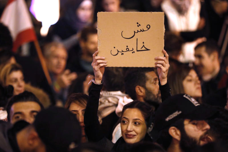 """Anti-government protesters holds an Arabic placard that reads:""""We are not fearing,"""" during a protest near the parliament square, in downtown Beirut, Lebanon, Sunday, Dec. 15, 2019. Lebanese security forces fired tear gas, rubber bullets and water cannons Sunday to disperse hundreds of protesters for a second straight day, ending what started as a peaceful rally in defiance of the toughest crackdown on anti-government demonstrations in two months. (AP Photo/Hussein Malla)"""