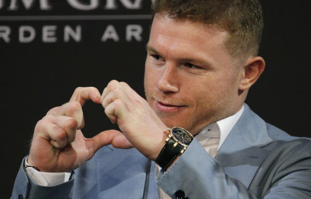 Canelo Alvarez motions to his family during a news conference Wednesday, Oct. 30, 2019, in Las Vegas. Alvarez is scheduled to fight Sergey Kovalev in a WBO light heavyweight title bout Saturday in Las Vegas. (AP Photo/John Locher)