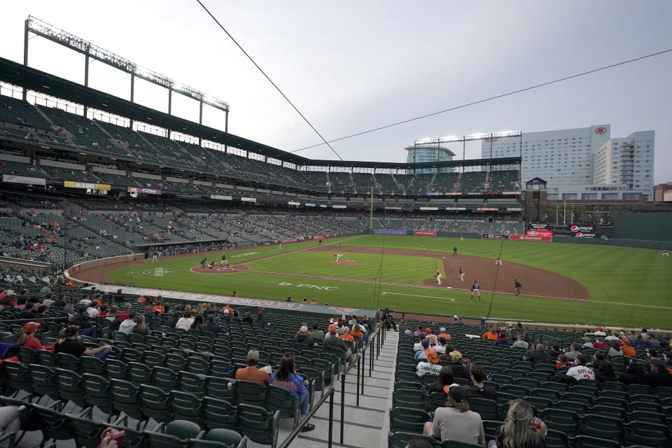 A socially distanced crowd watches on as Baltimore Orioles starting pitcher Bruce Zimmermann throws a pitch to the Boston Red Sox during the first inning of a baseball game, Saturday, April 10, 2021, in Baltimore. (AP Photo/Julio Cortez)