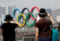 Women look at the giant Olympic rings, which are being temporarily removed for maintenance, at the waterfront area at Odaiba Marine Park in Tokyo
