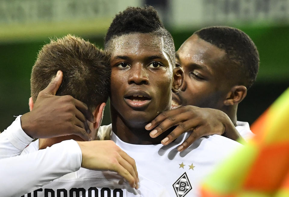 Moenchengladbach's Breel Embolo, center, is celebrated after he scored the opening goal during the German Bundesliga soccer match between Borussia Moenchengladbach and 1.FC Cologne in Moenchengladbach, Germany, Wednesday, March 11, 2020. It is the first Bundesliga match played behind closed doors without spectators due to the coronavirus outbreak. (AP Photo/Martin Meissner)