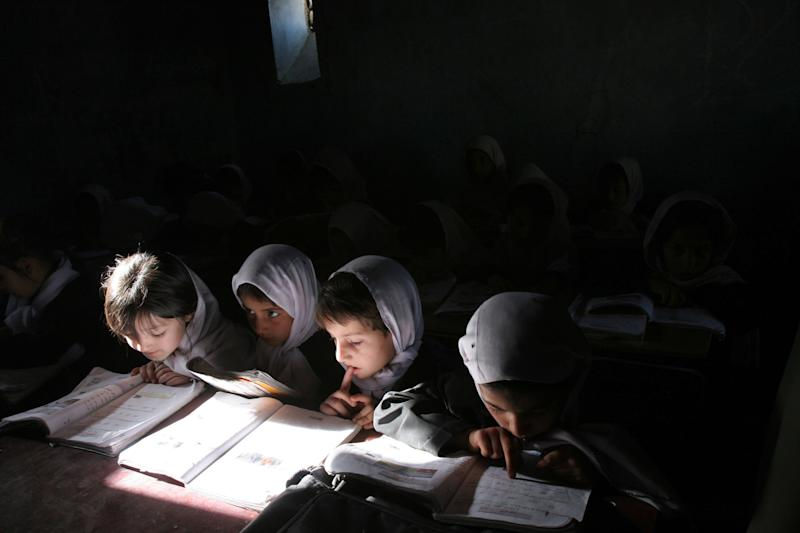 FILE - In this Tuesday, May 23, 2006 file photo, Afghan school girls read their lessons at the Aziz Afghan Secondary School in Kabul, Afghanistan. The Afghan government alleges the Taliban tried to poison students at girls' schools, causing outbreaks of sickness, and says 15 suspects have been arrested. (AP Photo/Rodrigo Abd, File)