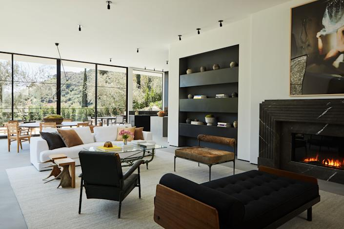 """<div class=""""caption""""> In the main living space, the Jean Prouvé S.C.A.L. metal and wood daybed (circa 1950) combines with a Jacques Adnet leather chair (from the 1960s). Both the Stag T stools and the brown Alchemy bench from <a href=""""https://carpentersworkshopgallery.com/"""" rel=""""nofollow noopener"""" target=""""_blank"""" data-ylk=""""slk:Carpenters Workshop Gallery"""" class=""""link rapid-noclick-resp"""">Carpenters Workshop Gallery</a> are by Rick Owens. The photograph above the fireplace is by Kerry Skarbakka and the silver wool Soumak rug is from <a href=""""https://www.lawrenceoflabrea.com/"""" rel=""""nofollow noopener"""" target=""""_blank"""" data-ylk=""""slk:Lawrence of La Brea"""" class=""""link rapid-noclick-resp"""">Lawrence of La Brea</a>. </div>"""