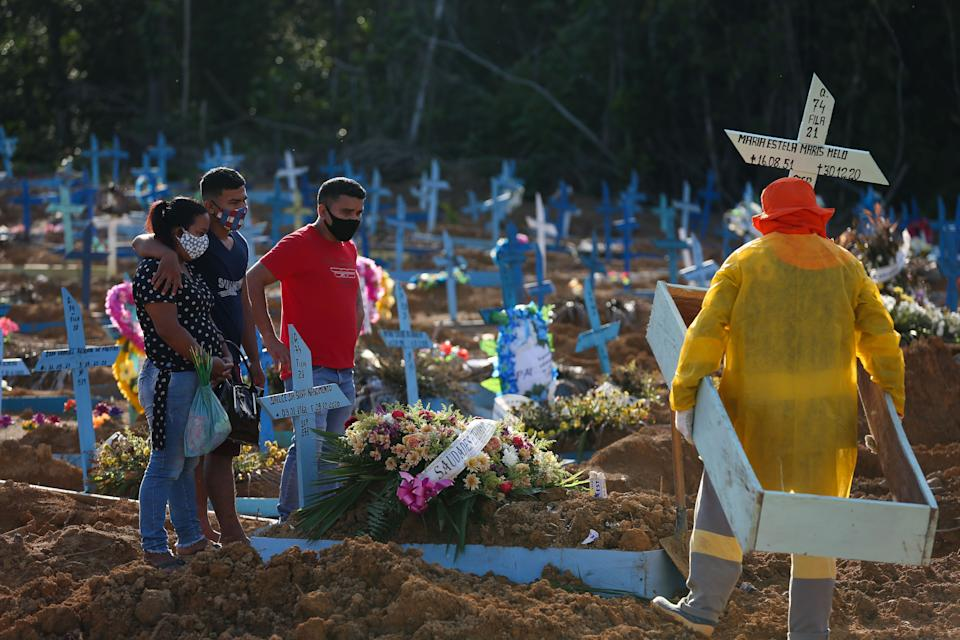 Relatives attend the funeral of COVID-19 victim Maria Estela Maris Melo, at the Nossa Senhora Aparecida cemetery in Manaus, Amazonas state, Brazil, on December 30, 2020. - Latin America and the Caribbean on Tuesday became the second region after Europe to top half a million deaths from Covid-19, according to an AFP count based on official tallies. There have been at least 500,800 deaths among the 29 countries in the region, with more than half of those in Brazil. (Photo by Michael DANTAS / AFP) (Photo by MICHAEL DANTAS/AFP via Getty Images)