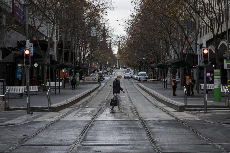 A man wearing a face mask walks across a road in Melbourne.