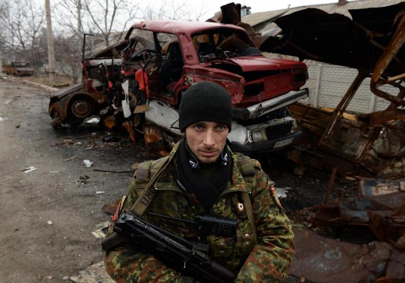 An armed supporter of the self-proclaimed People's Republic of Donetsk on December 16, 2014 in a street among destroyed houses and cars in Donetsk