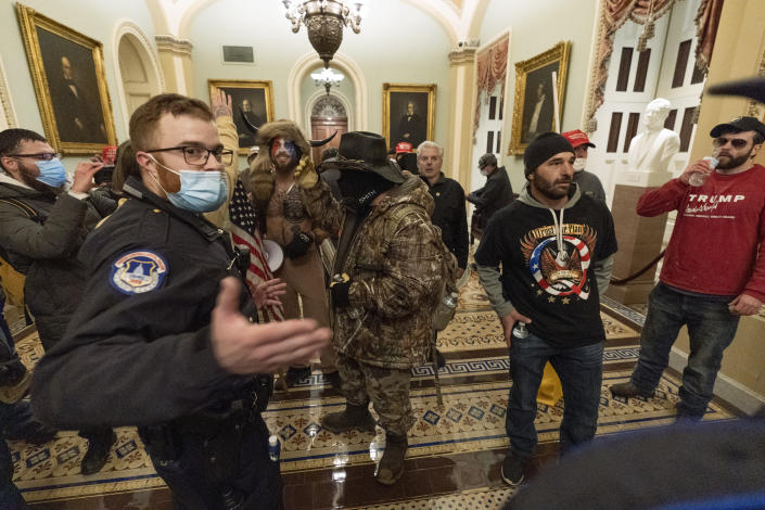 Supporter of President Donald Trump are confronted by Capitol Police officers outside the Senate Chamber at the Capitol, Wednesday, Jan. 6, 2021 in Washington. (AP Photo/Manuel Balce Ceneta)