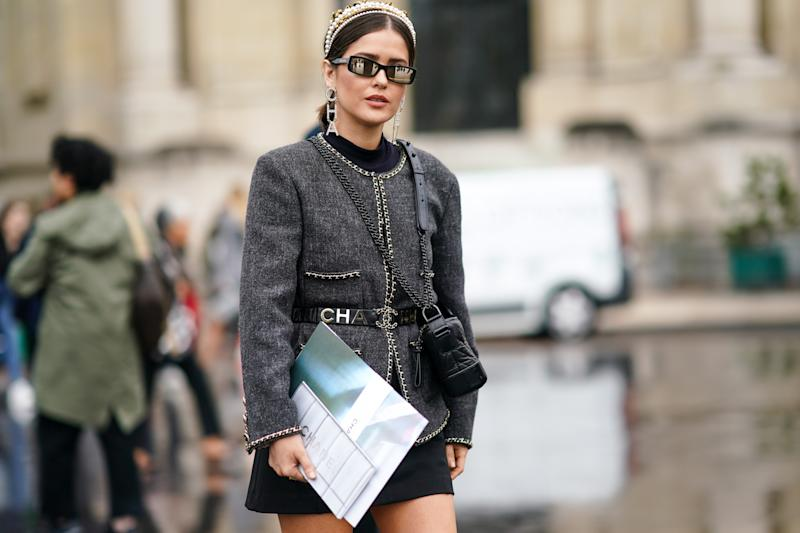 PARIS, FRANCE - OCTOBER 01: Paola Alberdi wears a pearl headband, Chanel earrings, Chanel mirrored sunglasses, a black hi-neck top, a Chanel grey jacket with a black Chanel belt, a black mini skirt, a black quilted bag, outside Chanel, during Paris Fashion Week - Womenswear Spring Summer 2020, on October 01, 2019 in Paris, France. (Photo by Edward Berthelot/Getty Images)