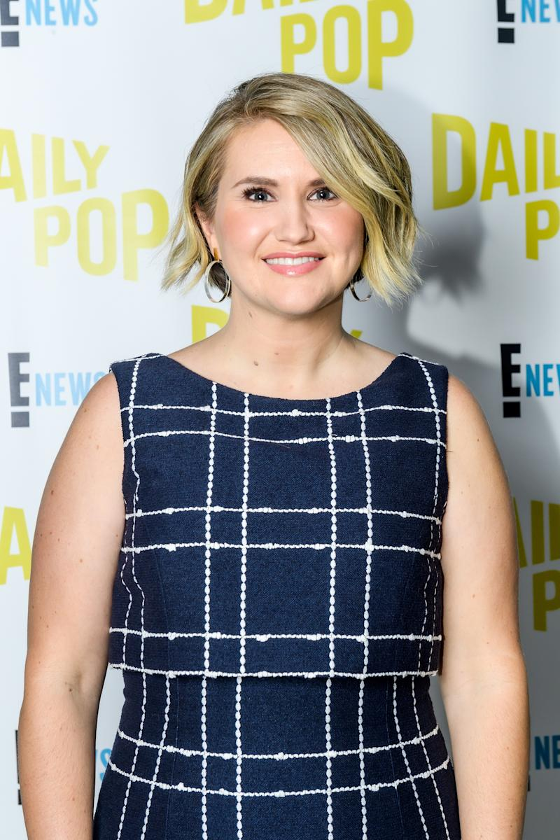 A photo of Brittany Runs a Marathon star and executive producer Jillian Bell wearing a blue and white dress at the Daily Pop studios.