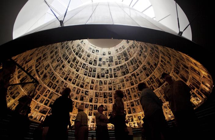 Visitors look at pictures of Jews killed in the Holocaust in the Hall of Names in the Yad Vashem Holocaust Memorial in Jerusalem, Sunday, April 7, 2013. The annual Israeli memorial day for the 6 million Jews killed in the Holocaust of World War II begins at sundown Sunday. (AP Photo/Sebastian Scheiner)