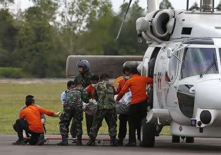 The body of an AirAsia Flight QZ8501 passenger, recovered from the Java Sea, is placed on a stretcher after arriving on a Japan Maritime Self-Defence Force helicopter at an airbase in Pangkalan Bun, Central Kalimantan, January 9, 2015. REUTERS/Darren Whiteside