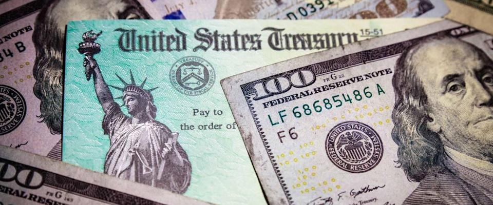 WASHINGTON DC - APRIL 2, 2020: United States Treasury check with US currency. Illustrates IRS stimulus check.