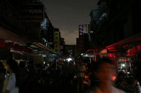 People walk on a street during a massive power outage in Taipei, Taiwan August 15, 2017. REUTERS/Stringer
