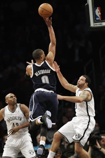Brooklyn Nets forward Jerry Stackhouse (42) and guard Deron Williams (8) watch as Oklahoma City Thunder guard Russell Westbrook (0) shoots in the first half of their NBA basketball game at Barclays Center, Tuesday, Dec. 4, 2012, in New York. (AP Photo/Kathy Willens)