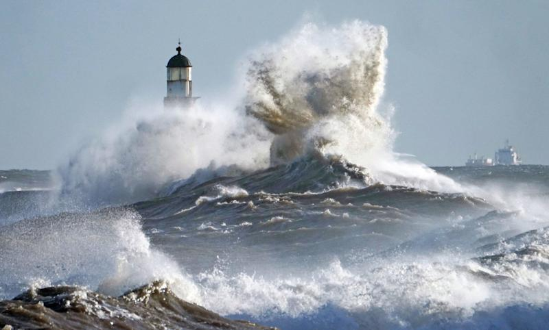 Waves crash against the pier wall at Seaham Lighthouse on the County Durham coast (PA)