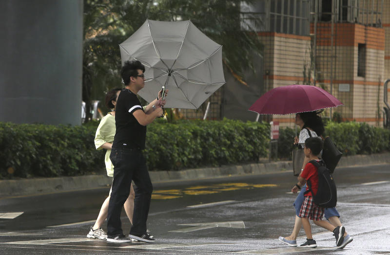 People cross a street in powerful gusts of wind generated by typhoon Ineng in Taipei, Taiwan, Saturday, Aug. 24, 2019. (AP Photo/Chiang Ying-ying)