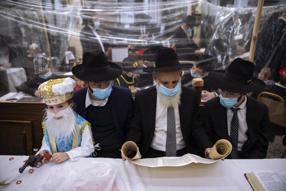 Jewish Ultra-Orthodox men and children, some wearing costumes and protective face masks, read the Book of Esther, which tells the story of the Jewish festival of Purim, at a synagogue separated by plastic partitions, follow new government measures to help stop the spread of the coronavirus, in Bnei Brak, Israel, Thursday, Feb 25, 2021. The Jewish holiday of Purim commemorates the Jews' salvation from genocide in ancient Persia, as recounted in the Book of Esther. (AP Photo/Oded Balilty)