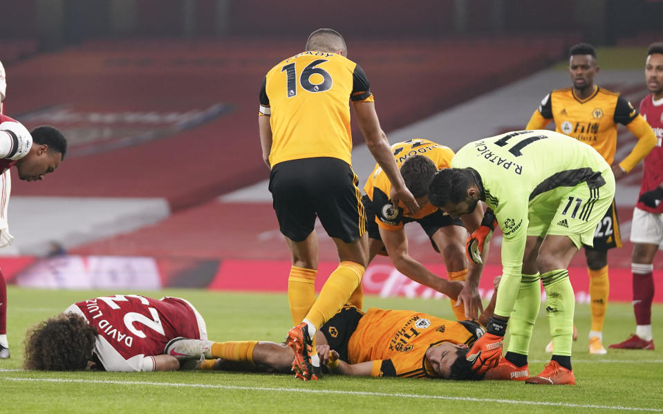 Players attend to Arsenal's David Luiz, left, and Wolverhampton Wanderers' Raul Jimenez following ahead clash during the English Premier League soccer match between Arsenal and Wolverhampton Wanderers at Emirates Stadium, London, Sunday, Nov. 29, 2020. (John Walton/Pool via AP)