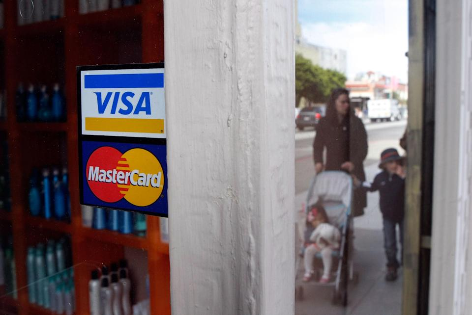 People walk by a window sticker advertising Visa and MasterCard credit cards. Photo: Justin Sullivan/Getty Images