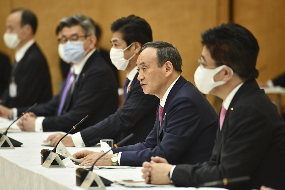 "Japanese Prime Minister Yoshihide Suga, second from right, speaks during a meeting of the coronavirus infection control headquarters at his office in Tokyo Friday, Jan. 22, 2021. Suga, in a speech earlier, said the vaccine is ""the clincher"" in the fight against the pandemic and vowed to start vaccinations as soon as late February, when a health ministry approval of the Pfizer vaccine, the first applicant, is expected. (Kazuhiro Nogi/Pool Photo via AP)"