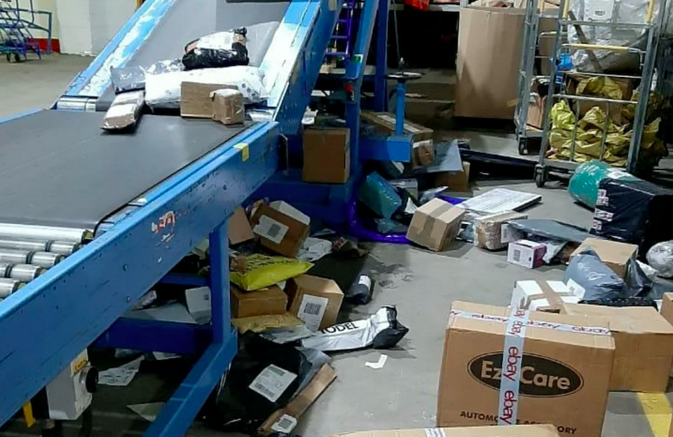 Some items in the Hermes depot are seen scattered on the ground after seemingly falling off the side of a conveyor belt (SWNS)