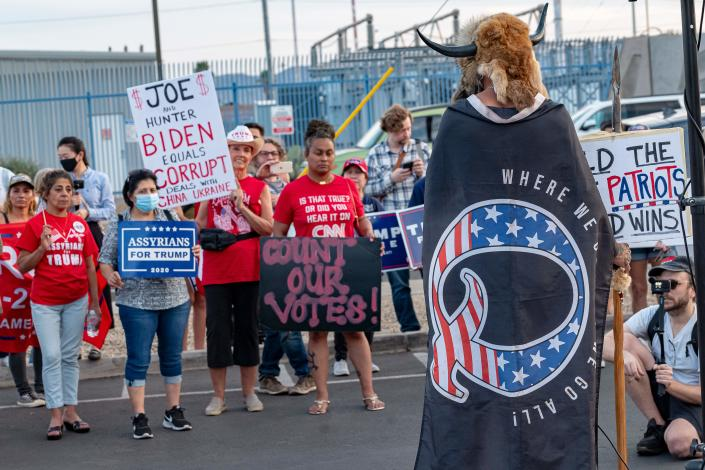 Jake A, 33, aka Yellowstone Wolf, from Phoenix, wrapped in a QAnon flag, addresses supporters of US President Donald Trump as they protest outside the Maricopa County Election Department as counting continues after the US presidential election in Phoenix, Arizona, on November 5, 2020. (Olivier Touron/AFP via Getty Images)